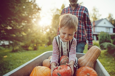 Cute boy and his father with pumpkins in autumn